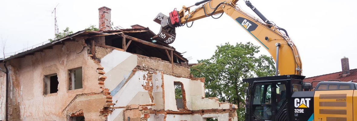 excavator demolishing home - omni contractors